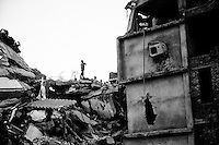 A rescue worker stands top of the collapsed building – Rana Plaza in Savar, near Dhaka, Bangladesh.