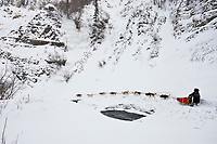 Karen Ramstead runs along the shelf ice near open water in the Dalzell Gorge on the trail to Rohn between Rainy Pass summit and Rohn during the 2010 Iditarod, Southcentral Alaska