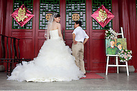 Bride Jiang Xiaoxiao, with her father, standing at the entrance to a banqueting suite, ready to welcome guests to her wedding reception. A humorous picture of the couple, dressed as Cultural Revolution era Red Guards, is on display beside them. Able to seat up to 5,000 people at one sitting, The West Lake Restaurant is the biggest Chinese restaurant in the world. Each week its diners, who staff are taught are 'the bringers of good fortune', devour 700 chickens, 200 snakes, 1,200 kgs of pork and 1,000 kgs of chillis. Its 300 chefs cook in five kitchens and its staff total more than 1,000.It is fully booked most nights.