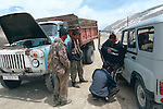 A jeep helps out a truck that is out of fuel by siphoning some off. The two vehicles met high in a mountain pass in the Pamir mountains of Tajikistan.