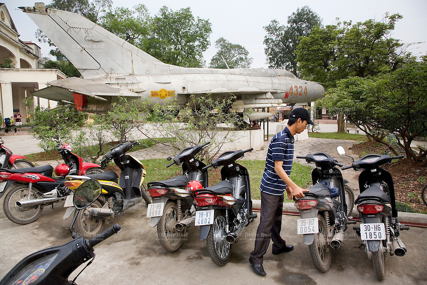 Vietnam. Hanoi. Military history museum. A russian-built Mig-21 fighter jet used by the army of North Vietnam during the war time. A young man parks his scooter. 04.04.09 © 2009 Didier Ruef