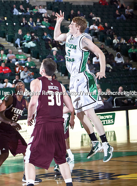 North Texas Mean Green center Ben Knox (15) goes up for a rebound in the game between the Texas State Bobcats and the University of North Texas Mean Green at the North Texas Coliseum,the Super Pit, in Denton, Texas. UNT defeated Texas State 85 to 62