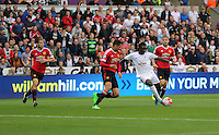 Pictured: Bafetimbi Gomis of Swansea (3rd L) marked closely by Chris Smalling of Manchester United, takes a shot a few inches away from the post Sunday 30 August 2015<br /> Re: Premier League, Swansea v Manchester United at the Liberty Stadium, Swansea, UK