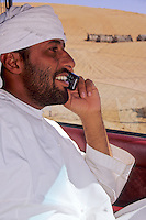 Wahiba Sands, Oman, Arabian Peninsula, Middle East - Bedouin Driver Using Cell Phone.