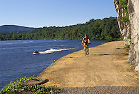 AJ2954, biking, bicycle, Maryland, Potomac River, Chesapeake and Ohio Canal Trail, Woman biking along the Potomac River on the recreation trail at the Chesapeake and Ohio Canal National Historic Park in the state of Maryland. Jet ski cruising along the river.