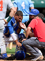 South Dade Buccaneers catcher Juan Aracena (17) gets check on by coach Bo Diaz and the trainer during the 42nd Annual FACA All-Star Baseball Classic on June 6, 2021 at Joker Marchant Stadium in Lakeland, Florida.  (Mike Janes/Four Seam Images)