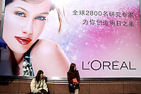 Women selling goods on the street under advertising for giant French cosmetics company L'Oreal on Huahai Lu in the French Concession.