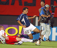 A Polish player tries to tackle the ball away from Landon Donovan. The USA lost 3-1 against Poland in the FIFA World Cup 2002 in Korea on June 14, 2002.