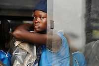 SIERRA LEONE, Kent, school girl in blue school uniform looking out a bus window /<br />