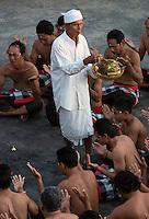 Bali, Indonesia.  Hindu Priest Sprinkles Water on dancers in the Kecak Dance, Arena adjacent to Uluwatu Temple.