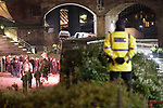 """© Joel Goodman - 07973 332324 . 03/11/2017 . Manchester , UK . Police watch on as fans of Tommy Robinson (real name Stephen Yaxley-Lennon ) queue for signed books at the launch of the former EDL leader's book """" Mohammed's Koran """" at Castlefield Bowl . Originally planned as a ticket-only event at Bowlers Exhibition Centre , the launch was moved at short notice to a public location in the city . Photo credit : Joel Goodman"""