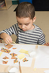 Education Preschool 3-4 year olds art activity gluing collages boy at work