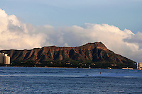 Beautiful afternoon view of Diamond Head with Waikiki Beach in the foreground and white puffy clouds in the background.