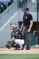 Charlotte Knights catcher Jeremy Dowdy (14) gives his pitcher a sign as home plate umpire Shane Livensparger looks on during the game against the Columbus Clippers at BB&T BallPark on May 27, 2015 in Charlotte, North Carolina.  The Clippers defeated the Knights 9-3.  (Brian Westerholt/Four Seam Images)