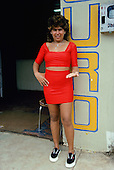 """Porto Velho, Brazil. """"Working girl"""" wearing skin tight bright red skirt and top showing her earnings in gold outside a gold dealer."""