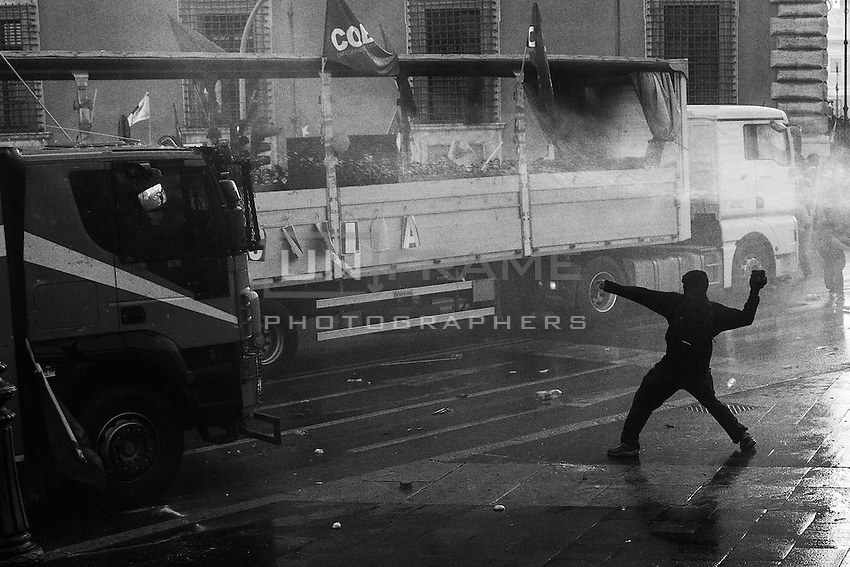 A hooded rioter throws a cobblestone against a water cannon police truck in piazza San Giovanni during the clashes triggered by organized violent fringes of protesters.  Rome, Italy. 15/10/2011