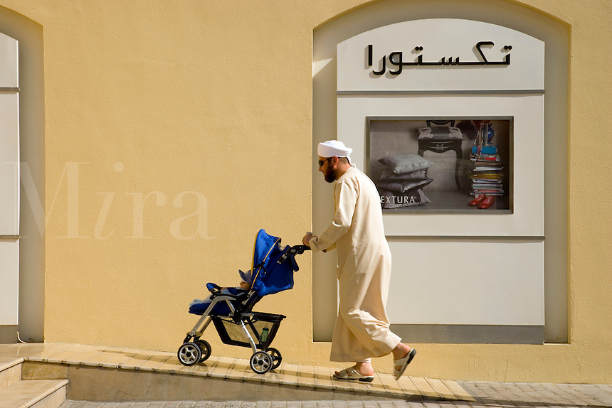 Dubai.  Local man pushes his son in a pushchair at entrance to shopping mall..