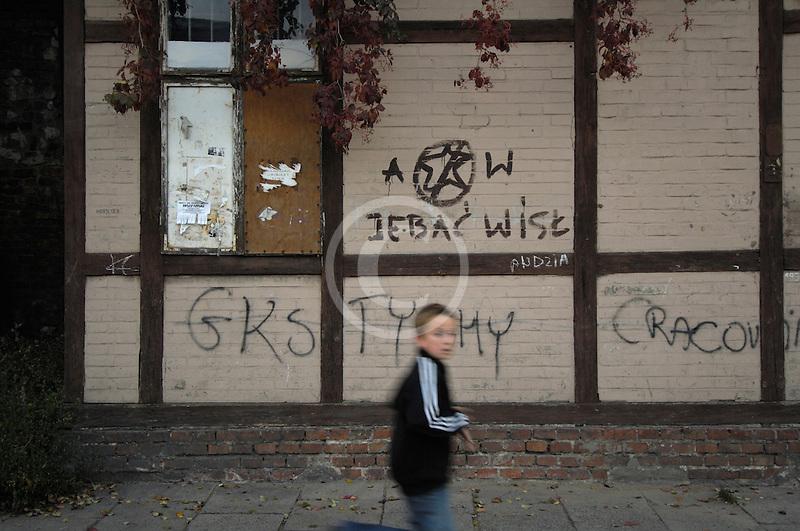 Poland, Krakow, Graffiti on wall, with boy walking past, Kazimierz