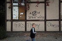Poland, Krakow, Graffiti on wall, with boy walking past, Kazimierz