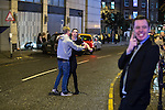 """© Joel Goodman - 07973 332324 . 17/12/2016 . Manchester , UK . A man holds his friend back in order to prevent a fight from escalating on Withy Grove . Revellers out in Manchester City Centre overnight during """" Mad Friday """" , named for being one of the busiest nights of the year for the emergency services in the UK . Photo credit : Joel Goodman"""