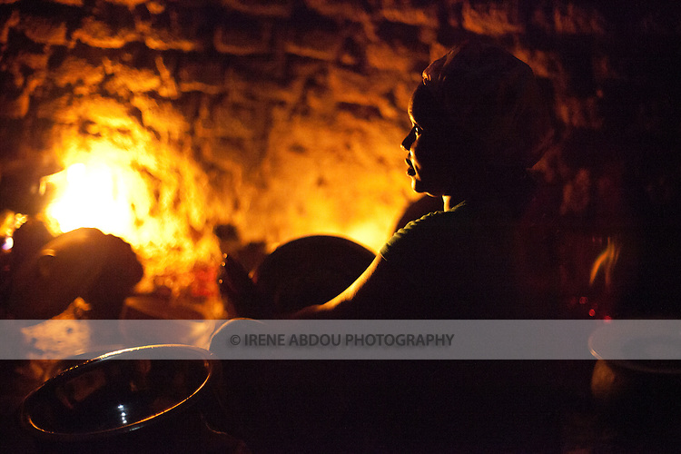 A woman in Djibo in northern Burkina Faso cooks dinner.  Without a stove or electricity, women throughout West Africa cook outside on an open fire.