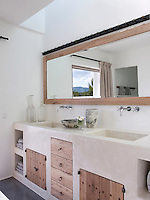 The bathroom has a stone double basin with built-in wooden drawers and cupboards. A long mirror reflects mountain views
