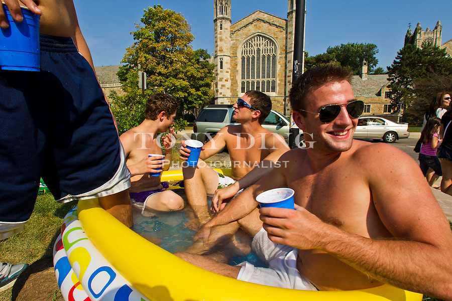 Alpha Delta Phi fraternity members Nate Snyder (cigar), Alex Cohen, and Evan Hendler, right, share an inflatable pool on their lawn across from the University of Michigan Law School, Friday, Sept. 2, 2011 in Ann Arbor, Mich. (Tony Ding for The New York Times)