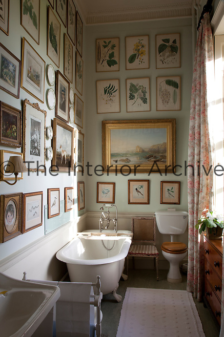 Botanical illustrations and paintings hang from the walls of this pale green bathroom