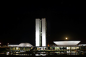 Brasilia, DF, Brazil. National Congress buildings at night with the full moon low over the dish.