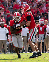 ATHENS, GA - SEPTEMBER 11: Kendall Milton #2 takes a handoff from Stetson Bennett #13 during a game between the Georgia Bulldogs and the UAB Blazers after a game between University of Alabama Birmingham Blazers and University of Georgia Bulldogs at Sanford Stadium on September 11, 2021 in Athens, Georgia.