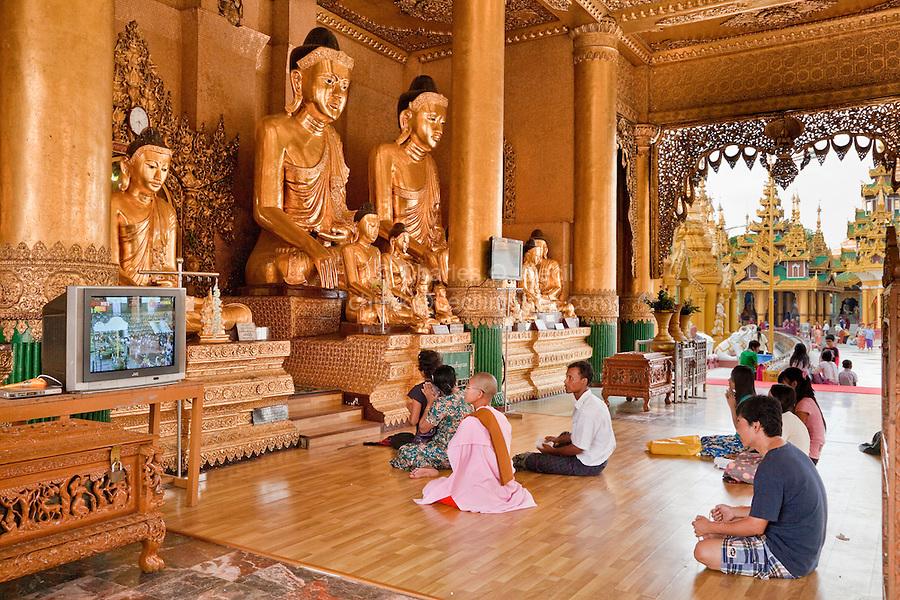 Myanmar, Burma.  Shwedagon Pagoda, Yangon, Rangoon.  Worshipers Praying at Buddha Shrine.