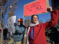 STAFF PHOTO BEN GOFF  @NWABenGoff -- 11/25/14 John Rule, left, and Joy Fox of Fayetteville hold signs while participating in a protest organized by the OMNI Center for Peace, Justice & Ecology in front of the Washington County Courthouse in Fayetteville on Tuesday Nov. 25, 2014. The demonstration was in response to the decision Monday night by the St. Louis County grand jury not to indict police officer Darren Wilson, who fatally shot Michael Brown in Ferguson, Mo.