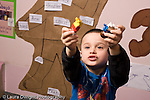 Education Preschool 3-4 year olds boy holding up people figures talking to himself horizontal