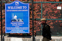 Paramilitary police pass in front of a sign for Srinagar Tourist Police, or the Friendly police as they call themselves. Kashmir,India. © Fredrik Naumann/Felix Features