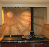 Custom kitchen sunburst stove backsplash in red and gold hand chopped 1cm marble tesserae.
