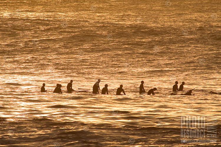 Surfers wait for the next set of waves at Waimea Bay, O'ahu.