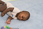 5 month old baby boy African American rolling over to reach for toy horizontal