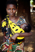 Izinga, Tanzania. Woman wearing printed cotton clothes carrying her baby tied to her in a cloth.