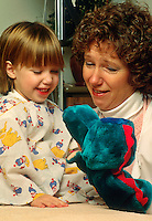 Pediatric nurse entertains a young patient with a hand puppet.
