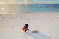 """A young boy puts his hands over his face near a dead fish on the shores of a beach in Funafuti. According to RNZ News in 2018, """"The European Union has lifted a so-called """"yellow card"""" it had given Tuvalu over its fisheries management. The lifting comes following improvements Tuvalu's made to fight illegal fishing. Tuvalu was issued the yellow card in December 2014, at risk of being considered a """"non-cooperating country."""" Fish caught by vessels operating in these countries can't be imported into the EU. The European Commission said it recognised Tuvalu's progress in addressing shortcomings in its fisheries governance. It said the EU had been able to help Tuvalu combat illegal fishing through a range of measures. ."""" Funafuti, Tuvalu. March, 2019."""