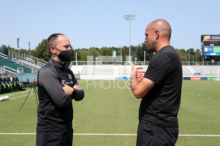 CARY, NC - SEPTEMBER 12: Head coach Mark Parsons of the Portland Thorns FC talks with assistant coach Sean Nahas of the North Carolina Courage before a game between Portland Thorns FC and North Carolina Courage at Sahlen's Stadium at WakeMed Soccer Park on September 12, 2021 in Cary, North Carolina.