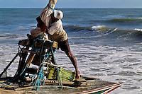A Brazilian fisherman (jangadeiro) fixes a boat mast on the beach of Prainha, Ceará state, northeastern Brazil, 8 March 2004. Jangadeiros, working on a unique wooden raft boat called jangada, keep the tradition of artisan fishing for more than four hundred years. However, being a fisherman on jangada is highly dangerous job. Jangadeiros spend up to several days on high-sea, sailing tens of kilometres far from the coast, with no navigation on board. In the last two decades jangadeiros have been facing up the pressure from motorized vessels which use modern, effective (and environmentally destructive) fishing methods. Every time jangadeiros come back from the sea with less fish.