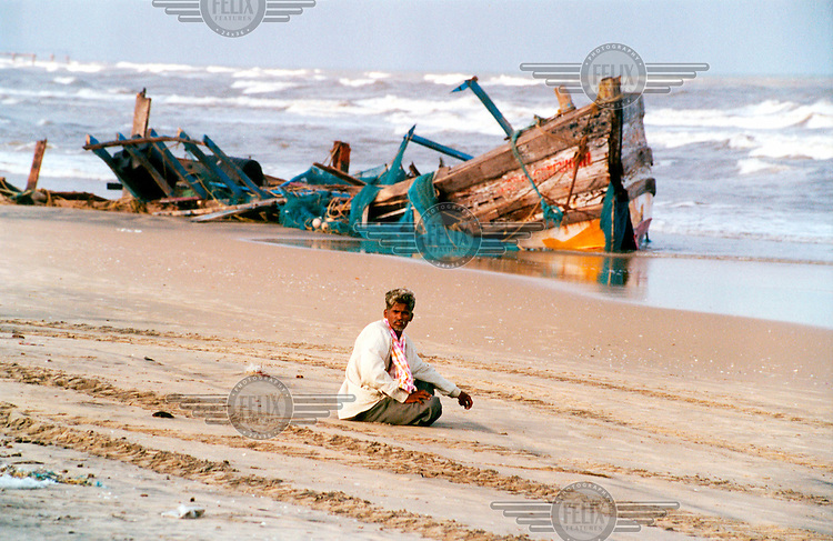 A man sits on the beach next to a scuttled fishing boat following the tsunami which struck South Asia on 26/12/2004..An underwater earthquake measuring 9 on the Richter scale triggered a series of tidal waves which caused devastation when they struck dry land. 12 countries were affected by the tsunami, with a combined death toll of over 150,000.