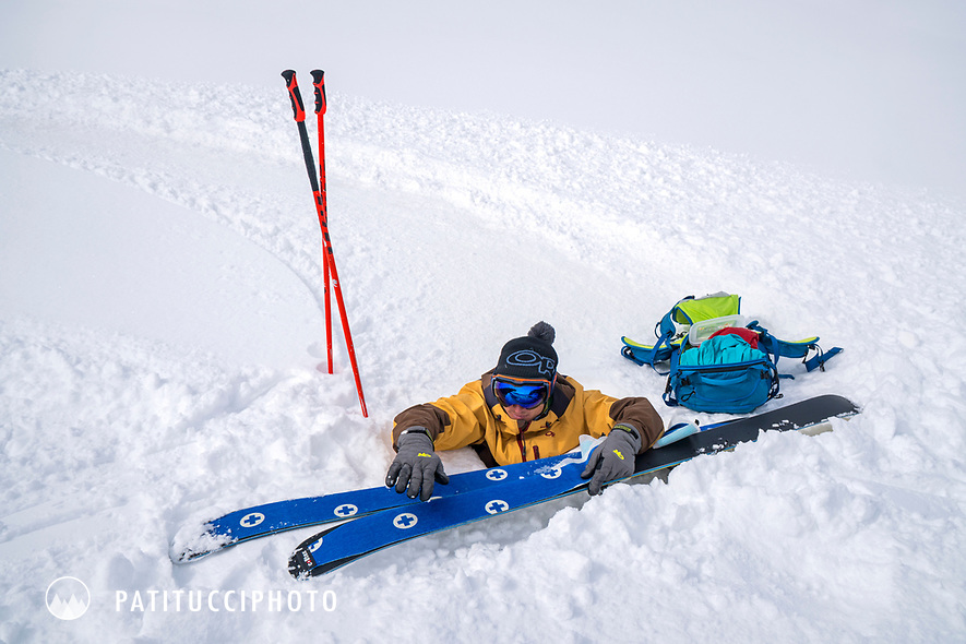 A skier steps out of his skis and discovers very deep snow so he playfully sits with his skis next to him. Kyrgyzstan