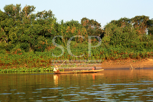 Pantanal, Brazil. Boy and small girl in a dugout canoe on the river with lush vegetation on the banks behind.