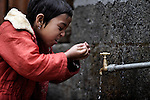 A young girl washes her face at the only water tap available at an orphanage in Pokhara, Nepal.