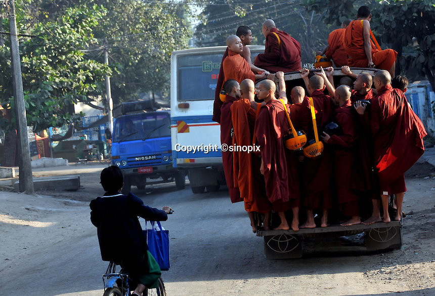"""Monks ride a bus, early morning, on the way to beg for food from villagers in Mandalay, Burma Oct 08.  Monks in this largely Buddhist country have to beg from villagers in order to feed themselves and in this city the government hand-outs stopped after the """"saffron revolution"""" of October 2007.<br /> <br /> Photo by Richard Jones"""