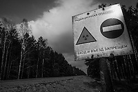 """Road sign through exclusion zone marked with signs that read  """"Radioactive danger. No trespassing"""".  Local people say that there are less and less signs left every year because government wants to use previously closed territories."""