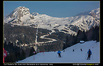 Italy, Dolomites.  <br /> The snow-covered foreground adds important light to an otherwise dark scene. Skiers descending Col Rodella to Canazei, Dolomites, Italy. Belvedere Ski Area is in background.
