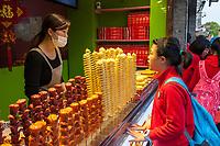 Yangzhou, Jiangsu, China.  Young Chinese Student at a Snack Stand in  Dong Guan Street.